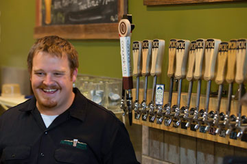 Brad Gilbert stands in front of Pateros Creek Brewing Company's line of draught beverages - which now includes Conundrum Coffee Nitro - a cold, non-alcoholic coffee drink.